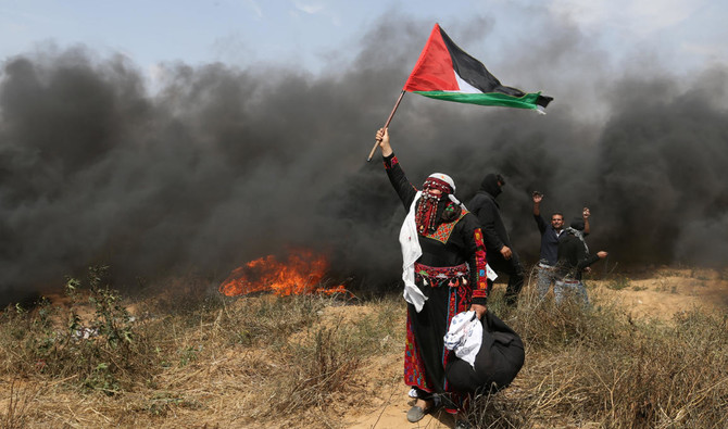 A woman demonstrator holds a Palestinian flag during clashes with Israeli troops during a protest at the Israel-Gaza border in the southern Gaza Strip. /(Reuters)