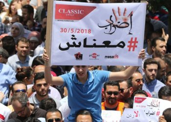 "Thousands of Jordanians take to the streets of Amman on May 30, 2018 to protest against a new income tax draft law which was approved by the government recently and sent to parliament for endoresement. Arabic slogan on poster placard reads: ""Strike/We are broke"". (AFP)"