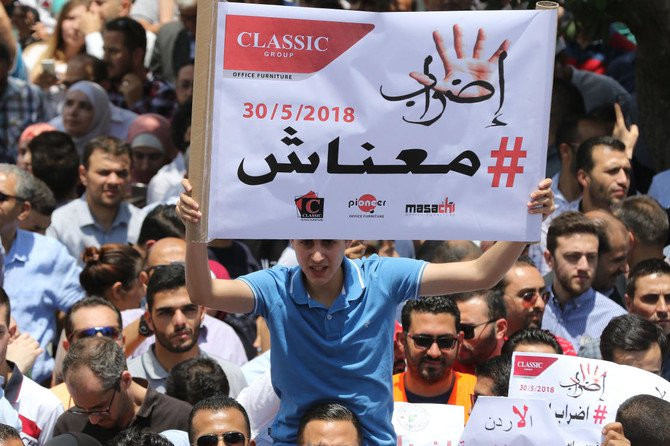 """Thousands of Jordanians take to the streets of Amman on May 30, 2018 to protest against a new income tax draft law which was approved by the government recently and sent to parliament for endoresement. Arabic slogan on poster placard reads: """"Strike/We are broke"""". (AFP)"""