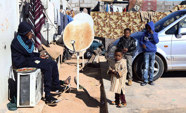 Young Libyans gather outside a makeshift house on January 4, 2015 in the capital Tripoli, at a refugee camp that hosts internally displaced people from the town of Tawargha, south of Mistrata. (AFP)