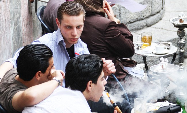 Young Syrian men smoke 'nargileh' or waterpipes, which are popular among locals and tourists, at a traditional cafe in Damascus' Old City. /AFP