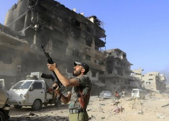 Syrian pro-government soldier fires his weapon. (AFP)