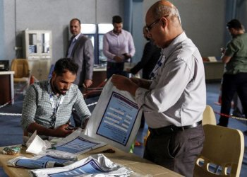 Electoral commission employees manually count ballots and compare them with electronic counting machine print-outs in Najaf on May 13. Iraq political uncertainty after the election, which was marred by a historically low turnout and allegations of fraud. (AFP)