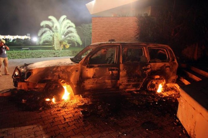 A vehicle sits smoldering in flames after being set on fire during the attack US consulate compound in Benghazi in 2012./ (AFP)