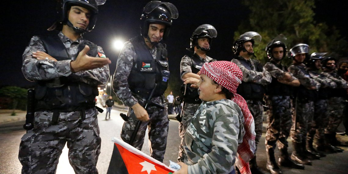 A child who came with his father holds a Jordanian flag while greeting policemen as they stand guard during a protest near Jordan Prime Minister's office in Amman, Jordan June 5, 2018. REUTERS/Muhammad Hamed