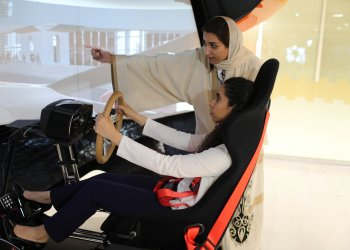 A driving instructor (back) teaches trainee Maria al-Faraj during a driving lesson on a 3D screen at Saudi Aramco Driving Center in Dhahran, Saudi Arabia, June 6, 2018. REUTERS/Ahmed Jadallah