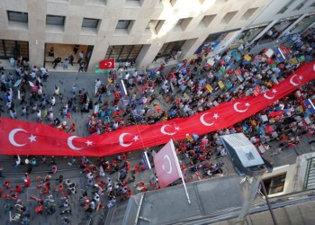 Supporters of Turkish President Tayyip Erdogan carry a huge Turkish flag during a pre-election gathering in Istanbul, Turkey, June 20, 2018. REUTERS/Huseyin Aldemir