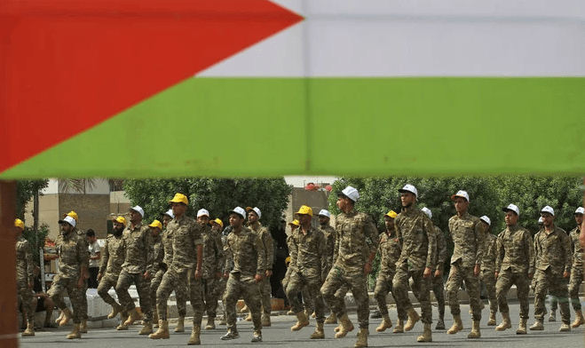 """Fighters of paramilitary units walk past a big Palestinian flag during a rally to mark """"Quds day"""" in Baghdad on Friday, June 8, 2018. (AFP)"""