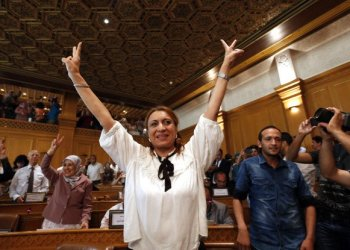 Souad Abderrahim, 54, flashes the V-sign after being elected as mayor of the Tunisian capital, Tunis. Souad Abderrahim of the Ennahdha party won the post in the second round of voting by the municipal council; the first time a woman holds the post. (AP)