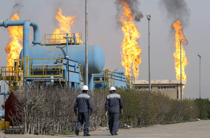 Iraqi oil technicians walk past a gas installation as flames resulting from the burning of excess hydrocarbons rise in the background at the Nahr Bin Omar natural gas field, north of the southern Iraqi port of Basra on January 22, 2018. Iraq will is expected to sign a memorandum of understanding with US energy company Orion on January 22 to tap gas at the oil field in the south of the country, the petroleum ministry said. The Nahr Bin Omar field, situated in the hydrocarbon-rich Basra province, is currently producing 40,000 barrels of oil a day, but only a small part of the gas from the field is being exploited. / AFP PHOTO / HAIDAR MOHAMMED ALI