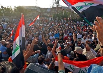 Iraqi protesters shout slogans and wave national flags, during a demonstration in the southern city of Basra, as they protest against poor services, unemployment and corruption. (AFP)