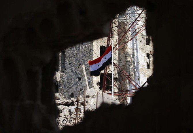 The Syrian national flag rises in the midst of damaged buildings in Daraa-al-Balad, an opposition-held part of the southern city of Daraa, on July 12, 2018. (File Photo: AFP/Mohamad Abazeed)