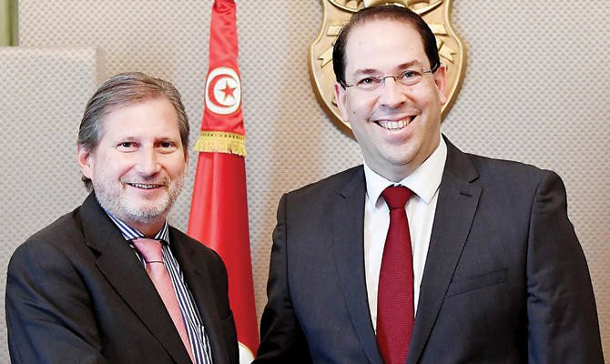 Tunisian Prime Minister Youssef Chahed shakes hands with the European Commissioner for European Neighborhood Policy and Enlargement Johannes Hahn, left, on Thursday in Tunis. AFP