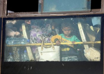 A Syrian child looks through the windows of a bus as displaced people from the Quneitra province wait at the Morak crossing point to be carried in the provinces of Idlib and Aleppo, in Morak, northwestern Syria, on July 21, 2018./ (AFP)