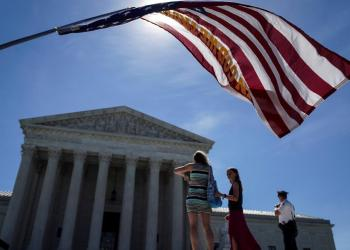 FILE PHOTO: A man holds a flag outside the U.S. Supreme Court in Washington, U.S., June 25, 2018. REUTERS/Toya Sarno Jordan/File Photo