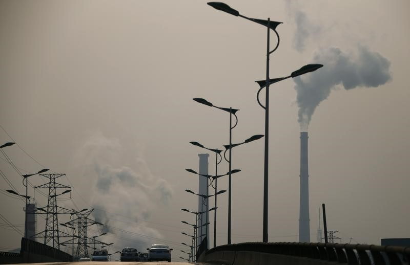 FILE PHOTO: Smoke rises from chimneys of a steel plant next to a viaduct on a hazy day in Tangshan, Hebei province February 18, 2014. REUTERS/Petar Kujundzic