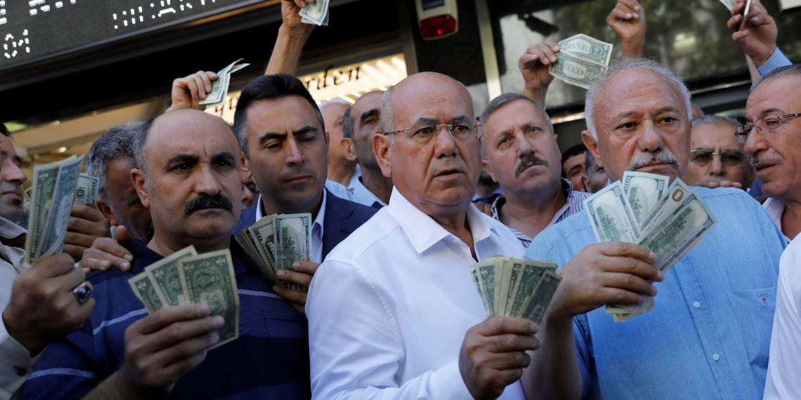 Businessmen holding U.S. dollars stand in front of a currency exchange office in response to the call of Turkish President Tayyip Erdogan on Turks to sell their dollar and euro savings to support the lira, in Ankara, Turkey August 14, 2018. REUTERS/Umit Bektas