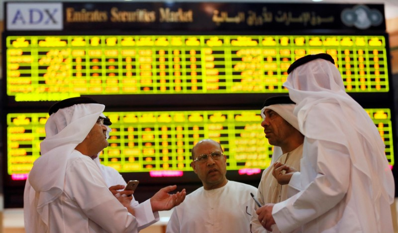 FILE PHOTO: Investors speak in front of a screen displaying stock information at the Abu Dhabi Securities Exchange, United Arab Emirates June 25, 2014. REUTERS/Stringer/File Photo