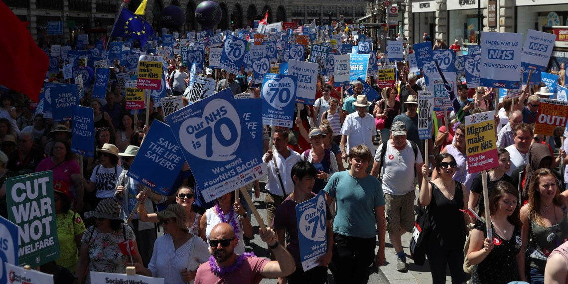 FILE PHOTO: Demonstrators hold placards during a march in support of the National Health Service, in central London, Britain, June 30, 2018. REUTERS/Simon Dawson