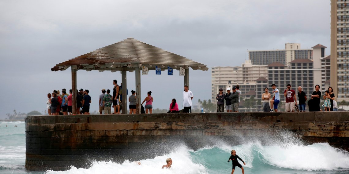 FILE PHOTO: Tourists watch surfers in Waikiki Bay as Tropical Storm Lane approaches Honolulu, Hawaii, U.S. August 24, 2018.  REUTERS/Terray Sylvester