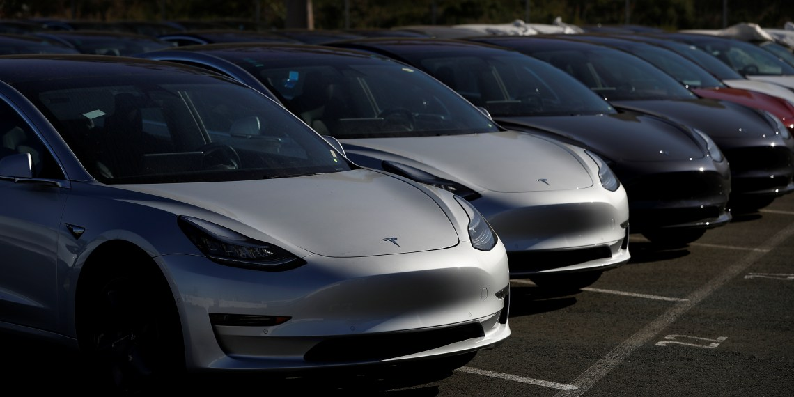 FILE PHOTO: A row of new Tesla Model 3 electric vehicles is seen at a parking lot in Richmond, California, U.S. June 22, 2018. Picture taken June 22, 2018. REUTERS/Stephen Lam