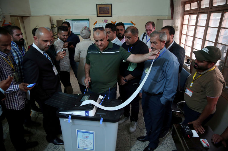 FILE PHOTO: Iraq's Independent High Electoral Commission employee closes a ballot box at a polling station during the parliamentary election in Baghdad, Iraq May 12, 2018. REUTERS/Abdullah Dhiaa al-Deen/File Photo