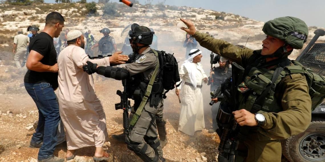 An Israeli soldier throws a sound grenade during a scuffle with Palestinian demonstrators at a protest against Israeli settlement construction, in the village of Ras Karkar, near Ramallah in the occupied West Bank, August 31, 2018. REUTERS/Mohamad Torokman