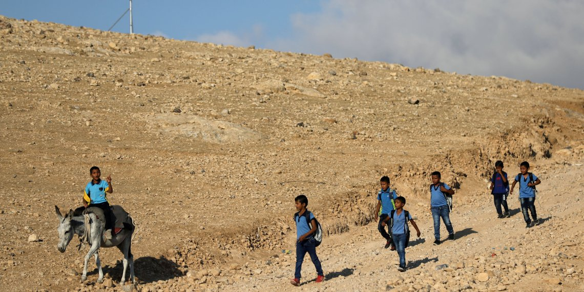 FILE PHOTO: A Palestinian schoolboy rides a donkey as he makes his way with other pupils to their school in the Bedouin village of Khan al-Ahmar, in the occupied West Bank, Sept. 6, 2018. REUTERS/Ammar Awad/File Photo