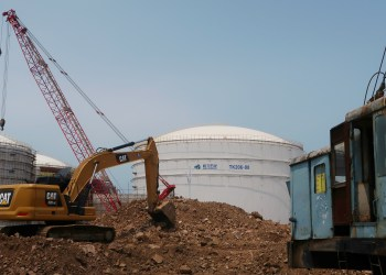 FILE PHOTO: A crude oil tank is seen behind a construction site at Hengli Petrochemical's new refining, petrochemical complex at Changxing island in Dalian, Liaoning province, China July 16, 2018. REUTERS/Chen Aizhu