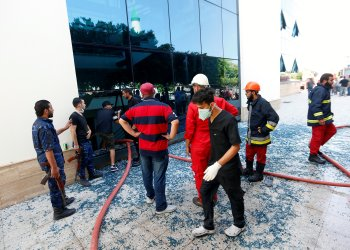 Firefighters and security personnel are seen at the headquarters of Libyan state oil firm National Oil Corporation (NOC) after three masked persons attacked it in Tripoli, Libya September 10, 2018. REUTERS/Ismail Zitouny