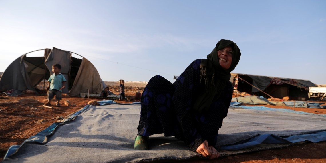 A newly displaced Syrian woman prepares a tent near a refugee camp in Atimah village, Idlib province, Syria September 11, 2018. REUTERS/Khalil Ashawi