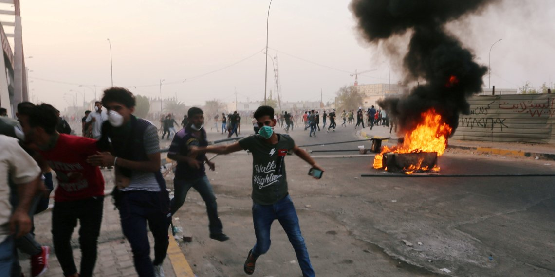 FILE PHOTO: Iraqi protesters run during a protest near the building of the government office in Basra, Iraq September 5, 2018. To match Analysis IRAQ-POLITICS/ REUTERS/Alaa al-Marjani/File Photo