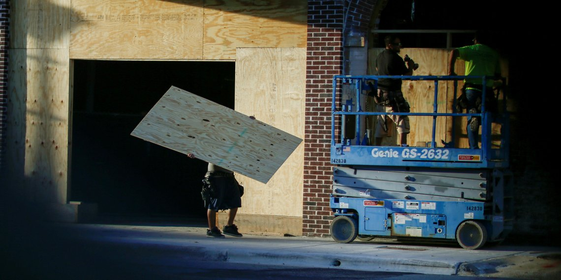 People put plywood up on the windows of a theatre before the arrival of Hurricane Florence in Greenville, North Carolina, U.S., September 12, 2018. REUTERS/Eduardo Munoz