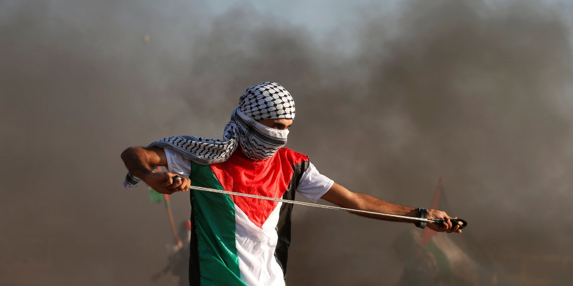 A Palestinian uses a sling to hurl stones at Israeli troops during a protest calling for lifting the Israeli blockade on Gaza and demand the right to return to their homeland, at the Israel-Gaza border fence, east of Gaza City September 14, 2018. REUTERS/Mohammed Salem