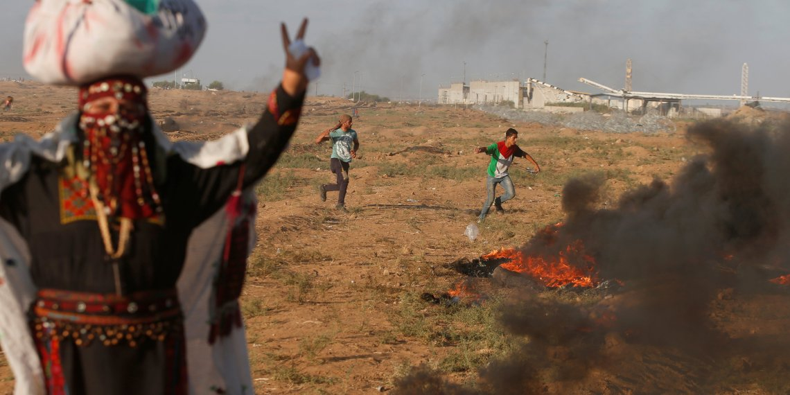 Palestinians hurl stones at Israeli troops during a protest calling for lifting the Israeli blockade on Gaza and demanding the right to return to their homeland, at the Israel-Gaza border fence, east of Gaza City September 14, 2018. REUTERS/Mohammed Salem
