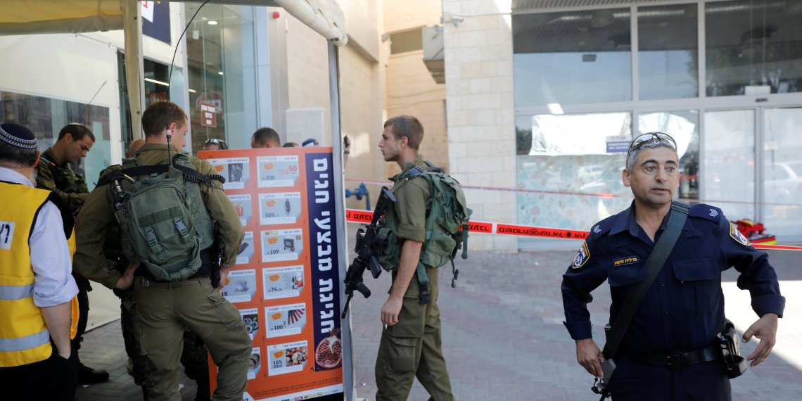 Israeli soldiers and a policeman work at the scene of a stabbing attack near a mall in the Gush Etzion Junction in the occupied West Bank, September 16, 2018. REUTERS/Ronen Zvulun