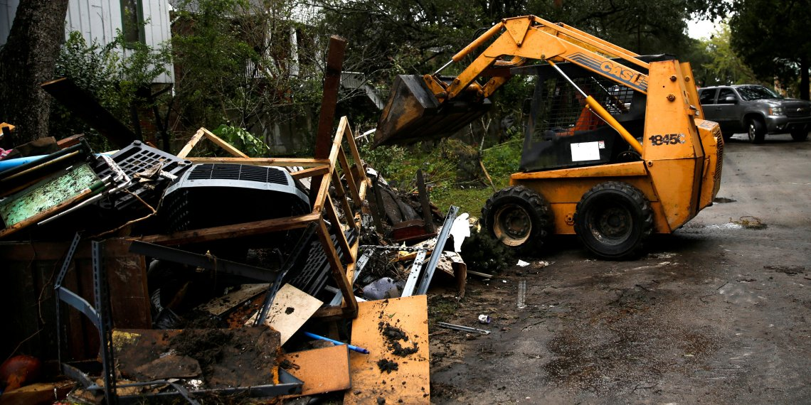 People use a backhoe to clean their house after the passing of Hurricane Florence in New Bern, North Carolina, U.S., September 16, 2018. REUTERS/Eduardo Munoz