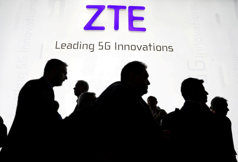 FILE PHOTO: Visitors pass in front of the Chinese telecoms equipment group ZTE Corp booth at the Mobile World Congress in Barcelona, Spain, February 26, 2018. REUTERS/Sergio Perez/File Photo