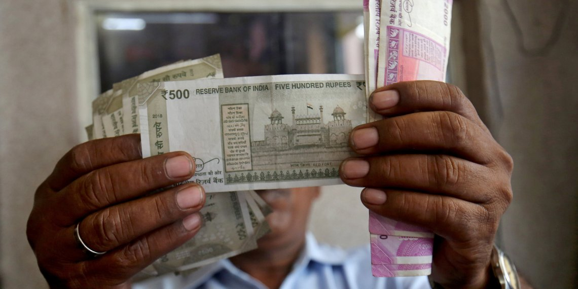 A cashier checks Indian rupee notes inside a room at a fuel station in Ahmedabad, September 20, 2018. REUTERS/Amit Dave