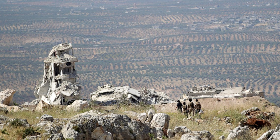 FILE PHOTO: Rebel fighters from the Ahrar al-Sham Islamic Movement walk on a hill in Jabal al-Arbaeen, which overlooks the northern town of Ariha, one of the last government strongholds in the Idlib province May 26, 2015. REUTERS/Khalil Ashawi/File Photo