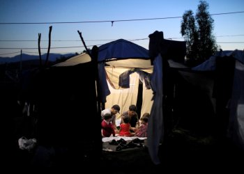 FILE PHOTO: Two migrant men and four babies sit inside a tent at a makeshift camp next to the Moria camp for refugees and migrants on the island of Lesbos, Greece, September 18, 2018. Picture taken September 18, 2018. REUTERS/Giorgos Moutafis/File Photo