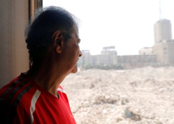 "Hisham Abu al-Ela, a 55-year-old businessman, looks out from window of his house which hasn't been demolished yet, in the so-called ""Maspero Triangle"", in Cairo, Egypt, September 13, 2018. REUTERS/Amr Abdallah Dalsh"