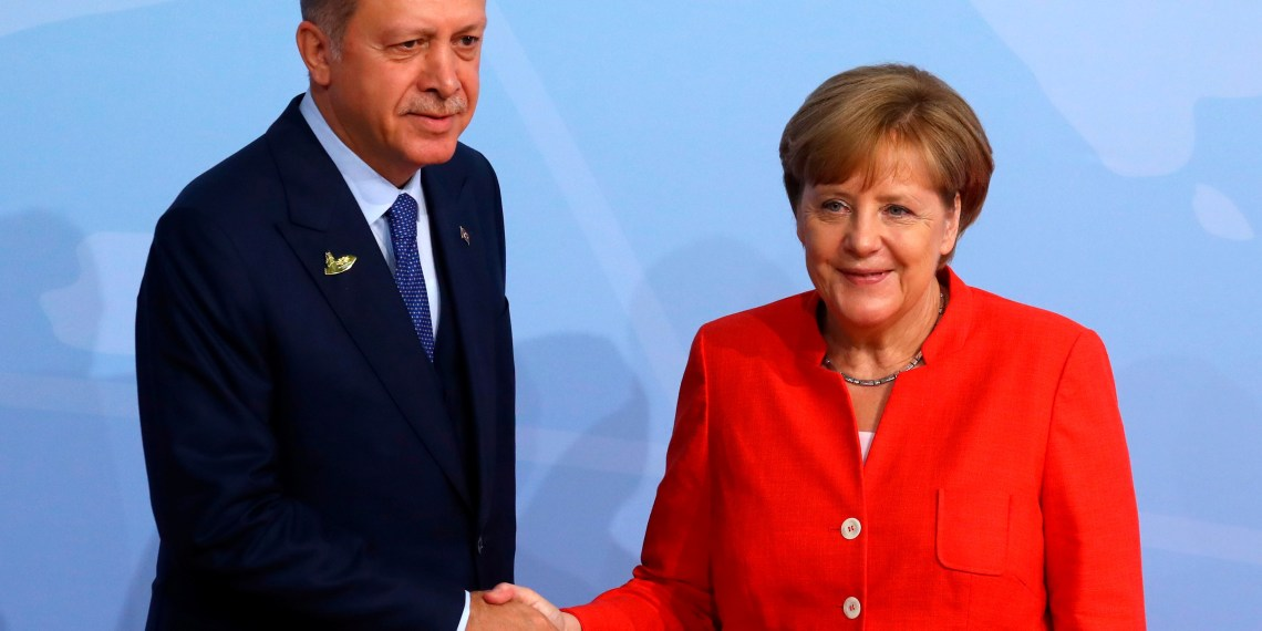 Turkish President Recep Tayyip Erdogan shakes hands with German Chancellor Angela Merkel as he arrives for the G20 leaders summit in Hamburg, Germany July 7, 2017. REUTERS/Kai Pfaffenbach