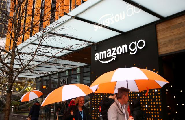 FILE PHOTO: People walk by the entrance to the new Amazon Go store at Amazon's Seattle headquarters in Seattle, Washington, U.S., January 29, 2018. REUTERS/Lindsey Wasson/File Photo