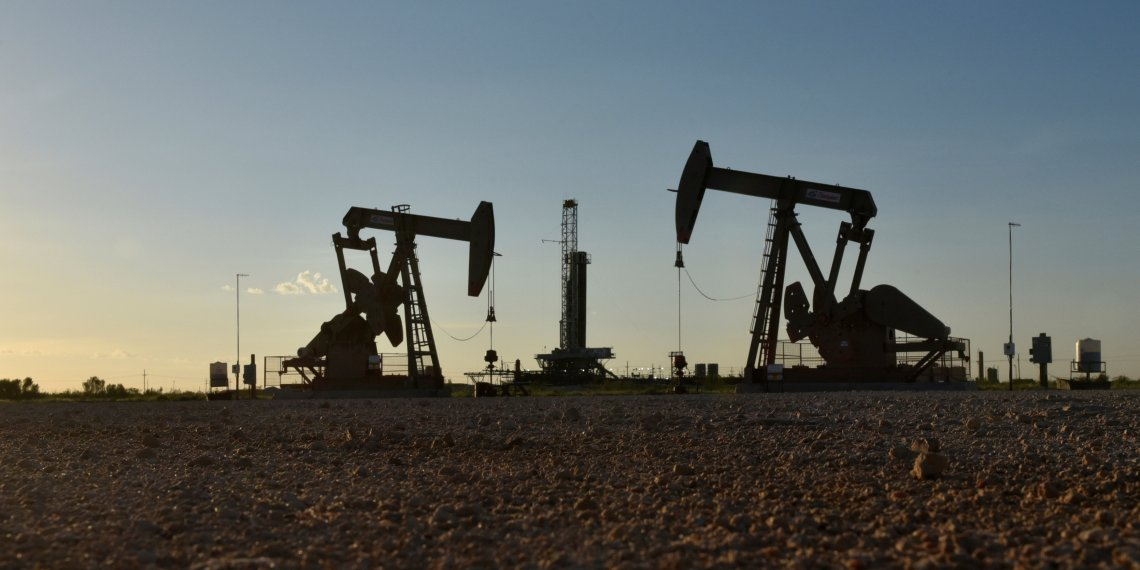 FILE PHOTO: Pump jacks operate in front of a drilling rig in an oil field in Midland, Texas U.S. August 22, 2018. REUTERS/Nick Oxford/File Photo