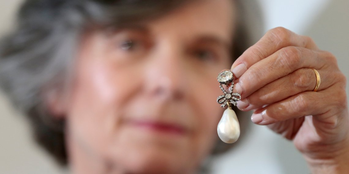 A member of Sotheby's staff holds a pearl and diamond pendant once belonging to Queen Marie Antoinette of France on display at Sotheby's in Dubai, UAE, October 9, 2018. Picture taken October 9, 2018.  REUTERS/Christopher Pike