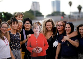 A group of working women in the Israeli high-tech industry pose with a cardboard cutout of German Chancellor Angela Merkel during a protest at Rabin Square in Tel Aviv, Israel October 10, 2018. REUTERS/Amir Cohen