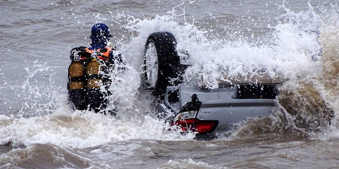 A wave crashes as a police diver examines a turned-over car in the sea off Sainte Maxime beach, France October 11, 2018 in this image obtained from social media. Alexandre Houisse via REUTERS