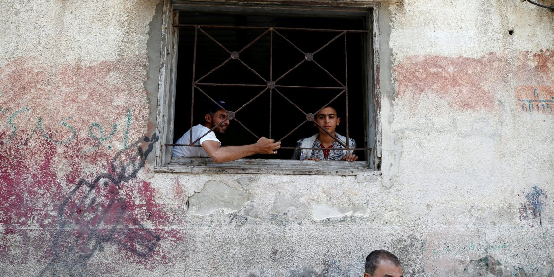 FILE PHOTO: Palestinians look out of their home at Al-Shati refugee camp in Gaza City September 3, 2018. REUTERS/Mohammed Salem/File Photo
