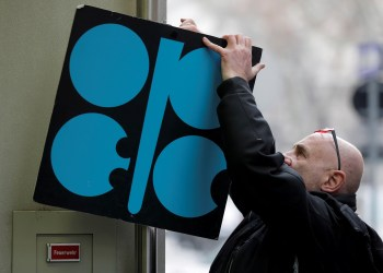 FILE PHOTO: A man fixes a sign with OPEC's logo next to its headquarters' entrance before a meeting of OPEC oil ministers in Vienna, Austria, November 29, 2017. REUTERS/Heinz-Peter Bader